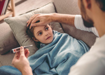 Krankes Kind auf Couch wird versorgt