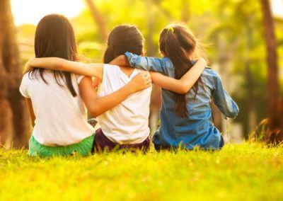 Drei Mädchen legen sich Arme über die Schulter