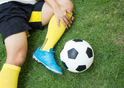 Fussballer hält sich das verletzte Knie