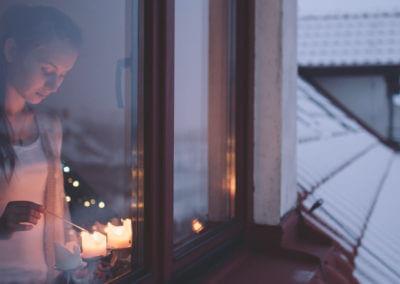 Frau zündet Kerzen auf Fensterbank an, draussen ist es dämmerig