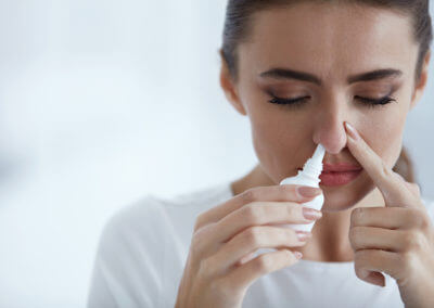 Frau benutzt Nasenspray