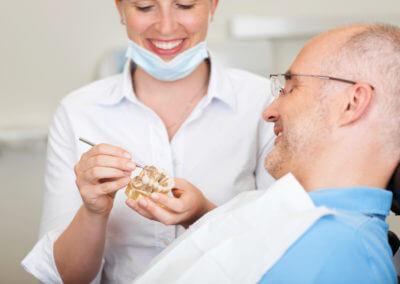 Zahnärztin erklärt Patienten auf der Liege ein Gebissmodell