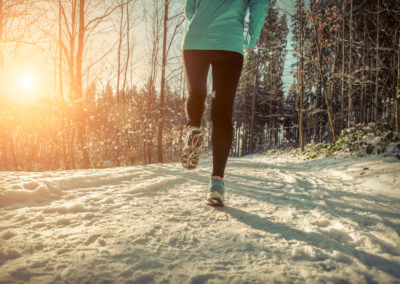 Joggerin läuft durch verschneiten Waldweg